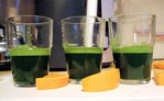Wheatgrass shots with slices of orange